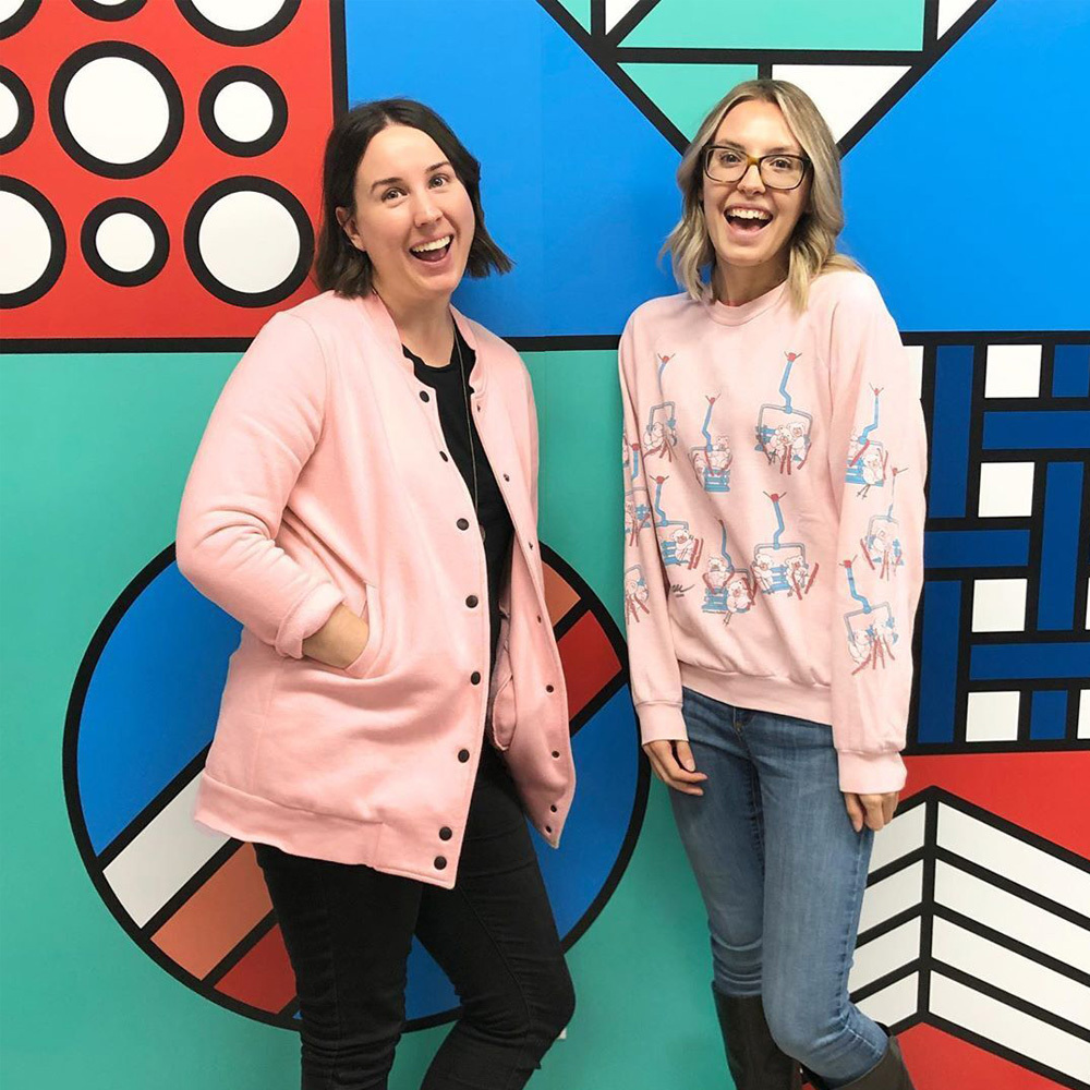 Laura and Liz wear matching pink sweaters