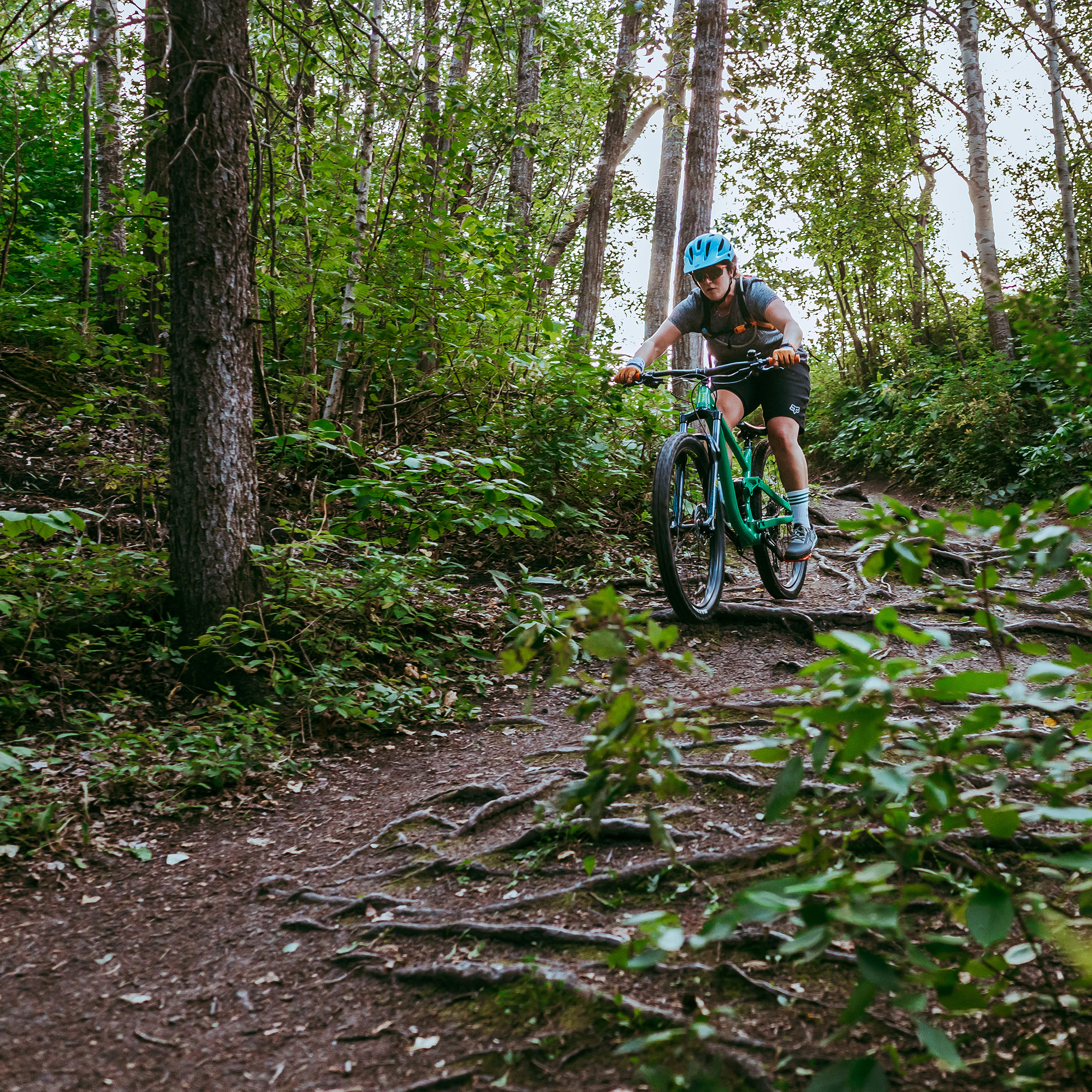 Emma rides her bike down a steep hill covered in tree roots