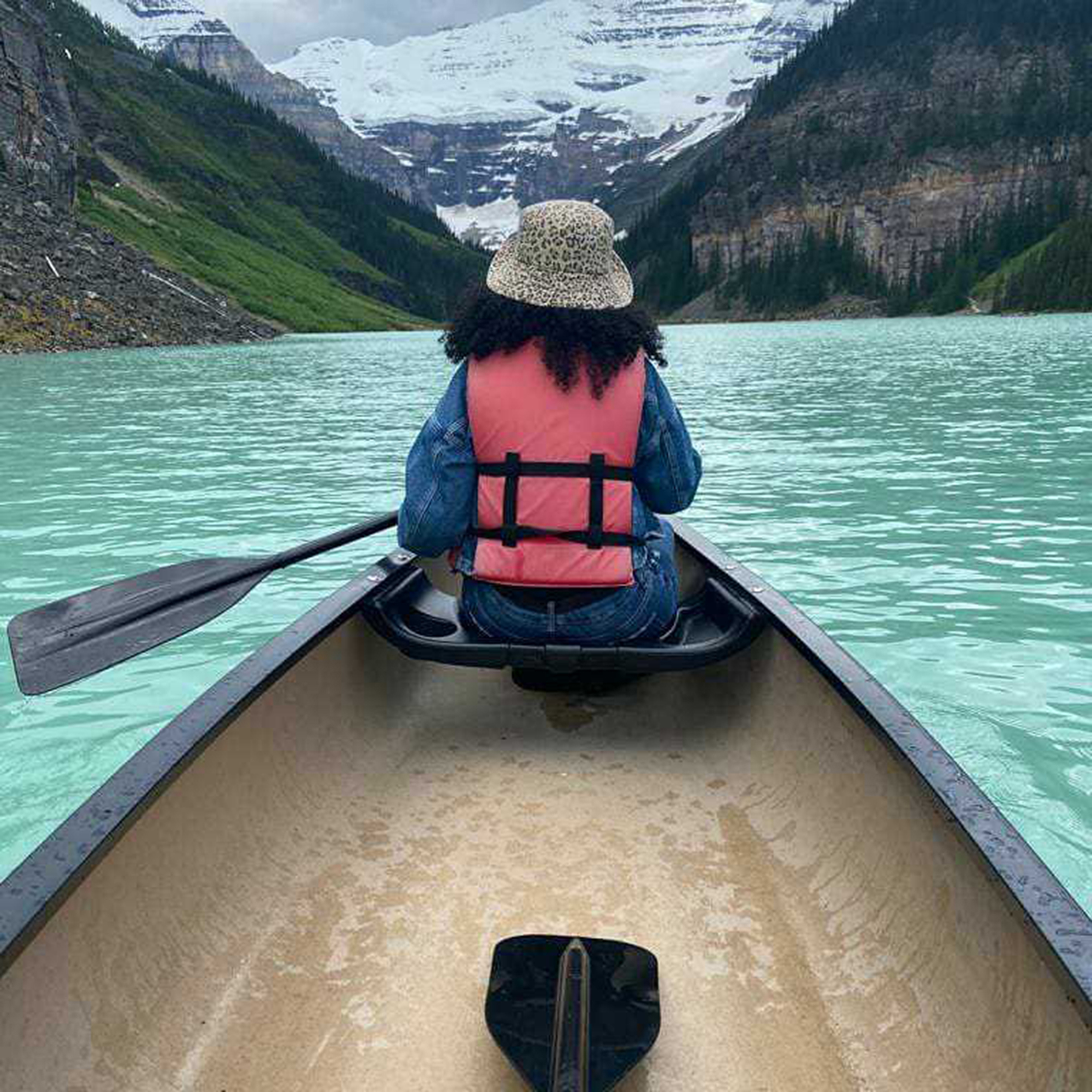 Firdous sitting in a canoe looking out at the lake and mountains.