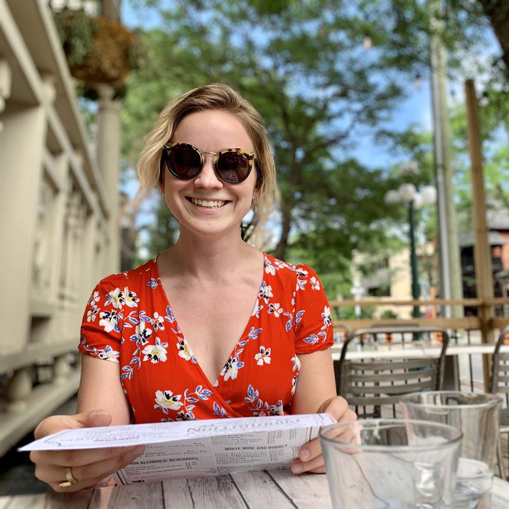 Sammy smiles while sitting on a restaurant patio